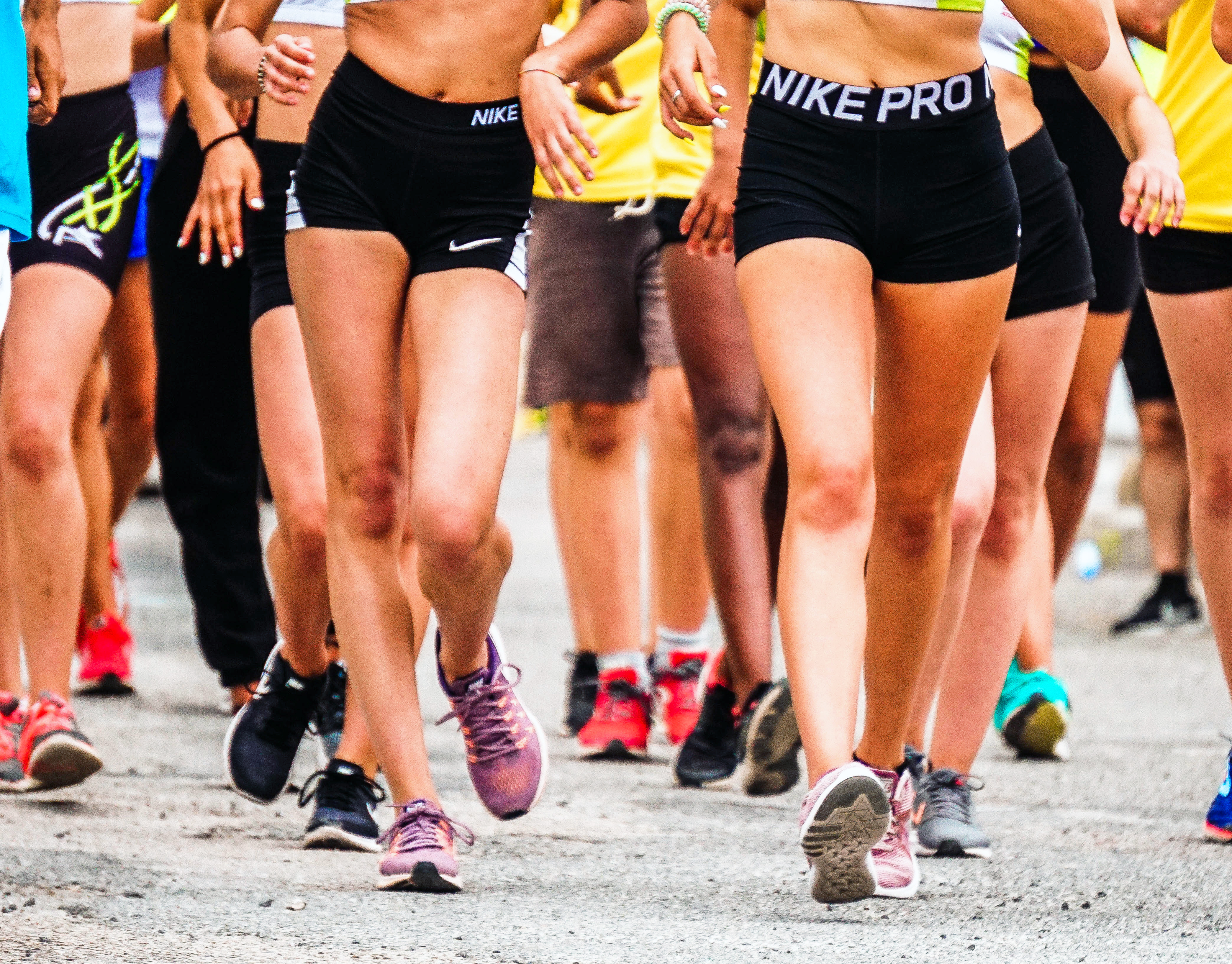 people running a race in shorts on pavement. run club at world of beer on mondays at 6 or 6:30